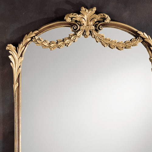 This carved wood framed vertical mirror is hand crafted in Louis XV style. Wall mirror has intricately carved frame richly embellished with scrolled leaf corners, a small elegant cartouche on the bottom center, and graceful leaf swags with rising leaf on the top. Louis XV mirror has a hand painted medium brown finish and antiqued gold leaf accents. This mirror is hand-crafted in Italy
