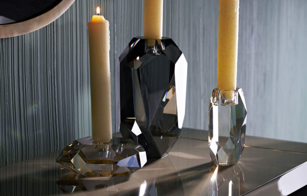 crystal accessories; ri-set of crystal candleholders. The champagne and smoke finishes on the diamond-like facets creates an arresting blend of elements and colors. The defined edges are highlighted by the contents of a taper candle. When grouped together, this set creates quite the lustrous trifecta.