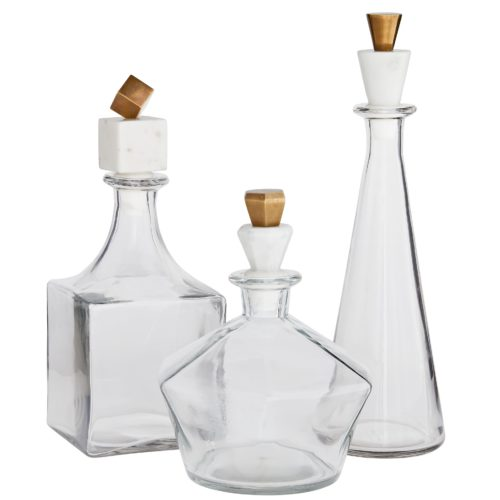 play on geometrics and the mix of materials that work together to create this decanter set is quite brilliant. Lead glass with a clear finish creates a crystalline effect that accentuates the sophisticated white marble and antique brass stoppers, each decanter bearing a unique shape. Evoking classic elements of style and design,