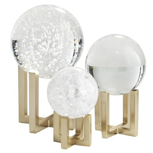 crystal orbs; these pieces feature their own qualities inclear, seeded and crackled textures. They are polished to a pristine orb and rest atop individual pedestals finished in antique brass.