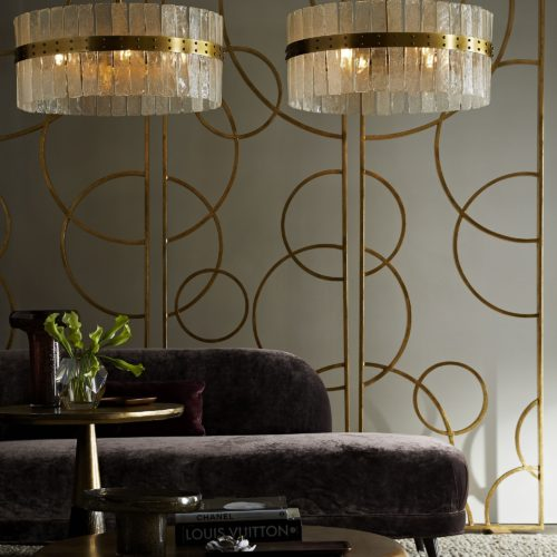 Elegant chandelier with gold leaf room screens. Accented beautifully with a purple velvet chaise.