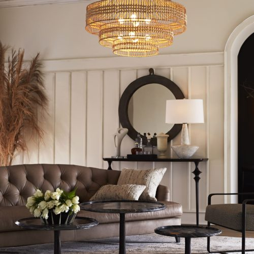 Modern living space with transitional elements featuring leather tufted couch and accent tables. Large round port mirror anchors this room with a classic touch.