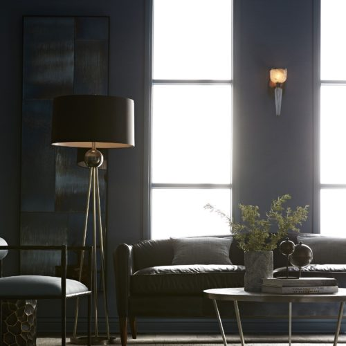 Elegant living room with blue and black hues. A warm and cozy space, inviting you to snuggle on the deep dark leather sofa.